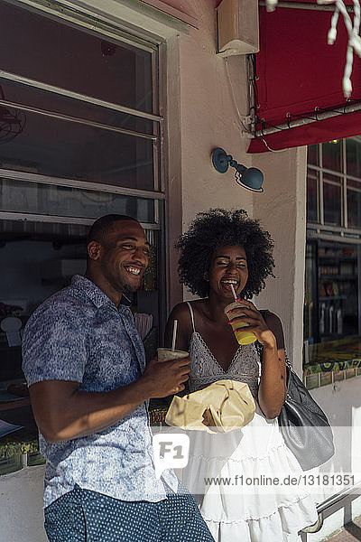 Happy young couple having a drink at a kiosk
