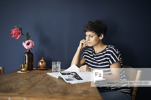 Woman at home sitting at wooden table reading a magazine