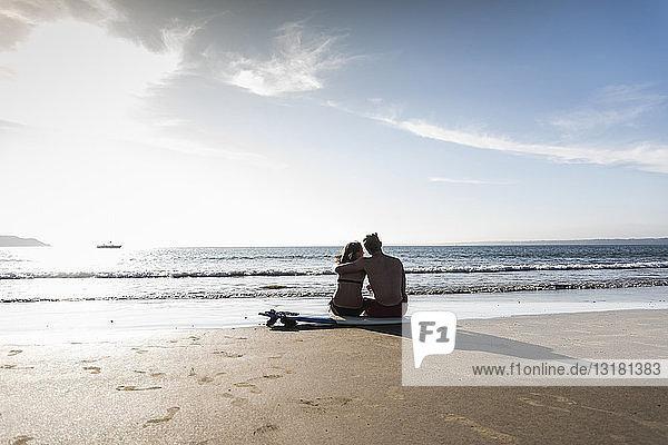 Frankreich,  Bretagne,  Rückansicht eines jungen Paares,  das auf einem Surfbrett am Strand sitzt