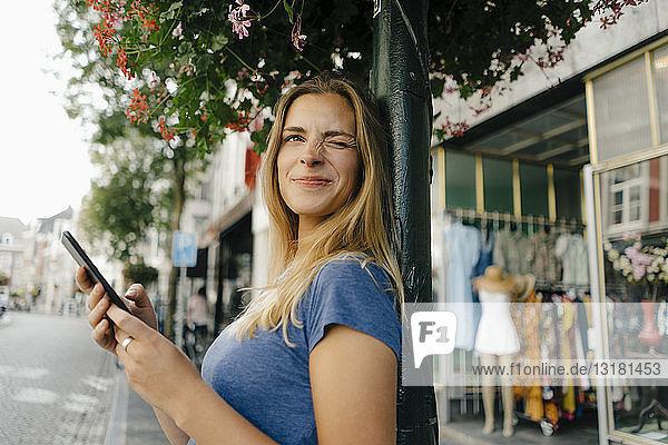 Niederlande  Maastricht  lächelnde junge Frau mit Handy in der Stadt funkelt