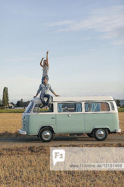 Glückliches Paar auf dem Dach eines Wohnmobils in ländlicher Landschaft