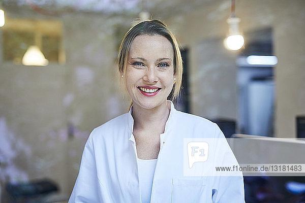 Porträt einer lächelnden Ärztin hinter einer Fensterscheibe