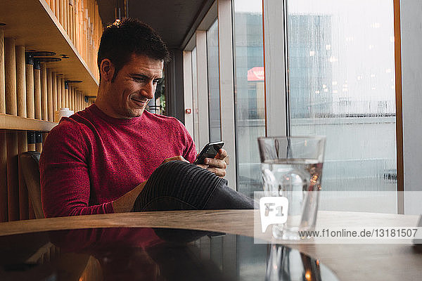 Businessman sitting in restaurant  using his smartphone