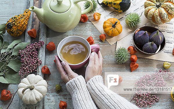 Frau wärmt im Herbst ihre Hände an einer Tasse Tee