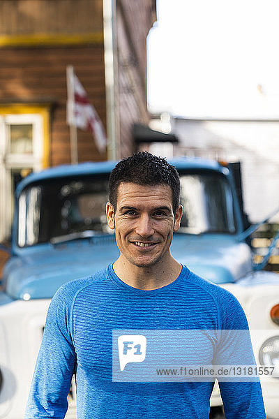 Portrait of smiling man in front of pickup truck