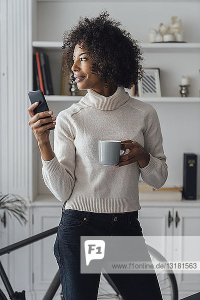 Mid adult freelancer standing in her home office  using smartphone  holding coffee cup