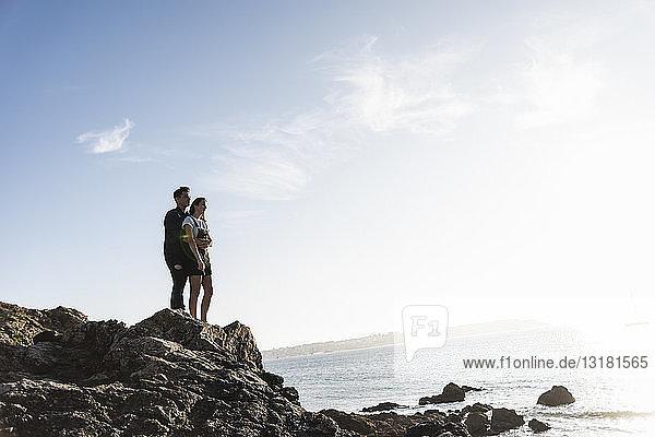 Frankreich  Bretagne  junges Paar steht bei Sonnenuntergang auf einem Felsen am Strand