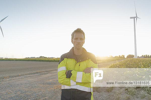 Porträt eines Ingenieurs  der auf einem Feldweg an einem Windpark steht