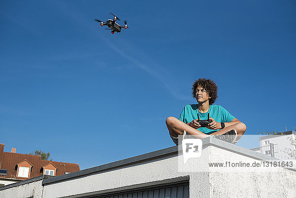 Boy navigating a flying drone  sitting on garage roof