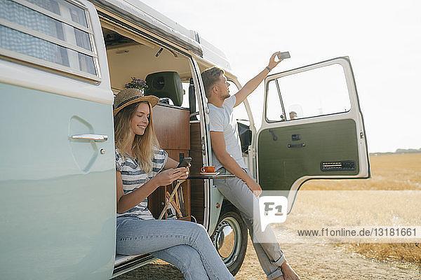 Junges Paar mit Mobiltelefonen entspannt sich im Wohnmobil in ländlicher Umgebung
