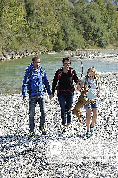 Familienwanderung mit Rucksäcken und Hund an der Isar  Oberbayern  Deutschland