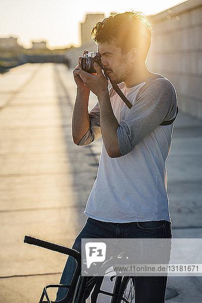 Junger Mann mit Pendler-Fixie-Fahrrad beim Fotografieren bei Sonnenuntergang