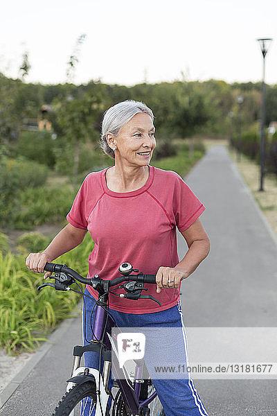 Senior woman with bicycle on bicycle lane