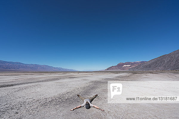 USA  California  Death Valley  man lying on ground in the desert