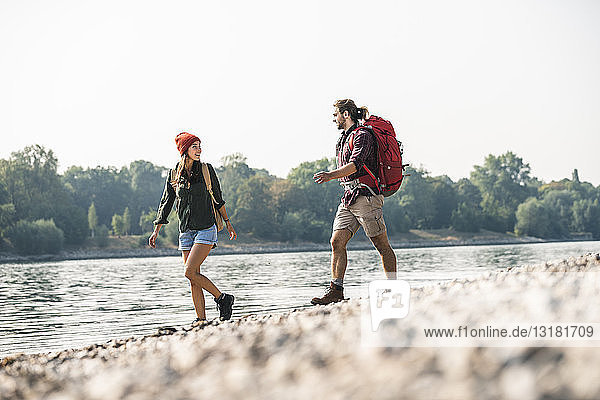 Junges Paar mit Rucksäcken beim Spaziergang am Flussufer