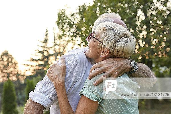Glückliches älteres Paar umarmt sich im Freien
