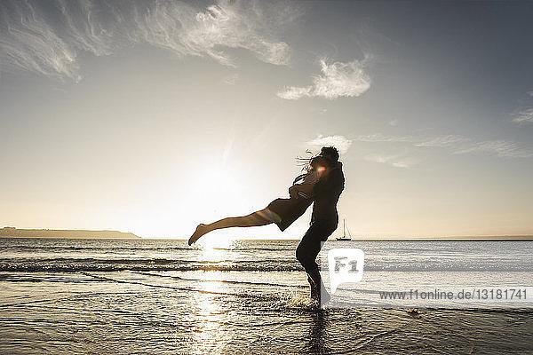 Frankreich  Bretagne  glückliches junges Paar umarmt sich bei Sonnenuntergang am Strand