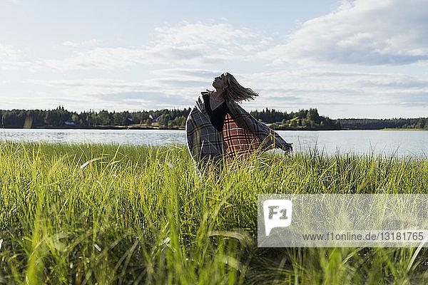 Finnland  Lappland  Frau mit einer Decke am Seeufer