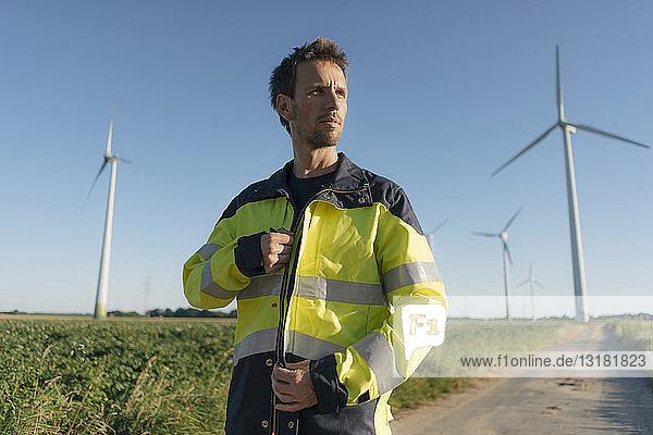Porträt eines Ingenieurs auf dem Feldweg in einem Windpark