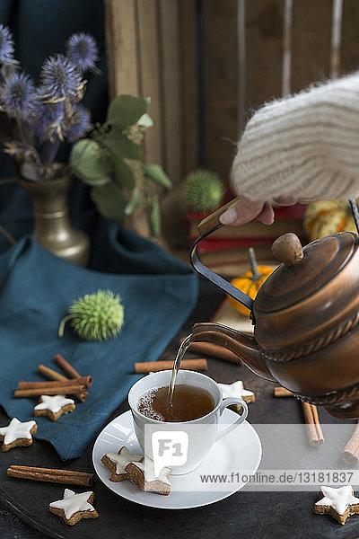 Die Hand einer Frau gießt Tee in eine Tasse