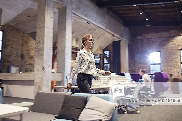 Busy woman walking in modern office  blurred motion