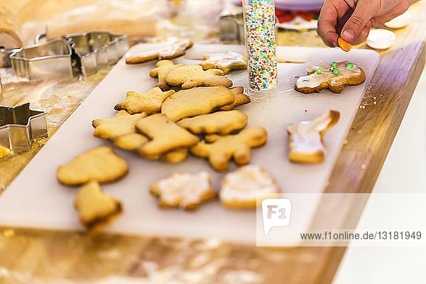 Girl's hand decorating Christmas cookies