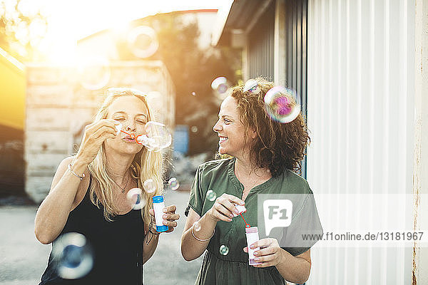 Two happy women blowing soap bubbles outdoors