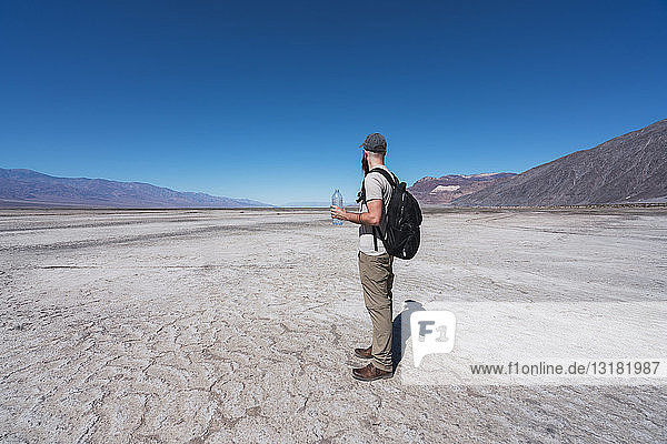 USA  California  Death Valley  man with backpack and water bottle standing in desert looking at distance