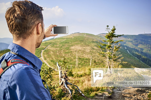 Man taking picture with his cell phone during hiking trip in the mountains