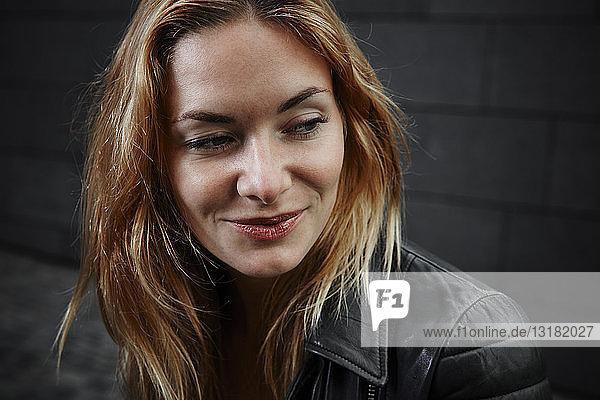 Porträt einer lächelnden jungen Frau in Biker-Jacke
