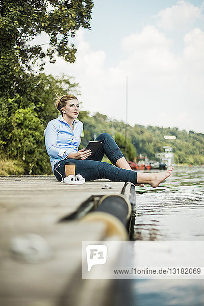 Woman sitting on jetty at a lake with tablet