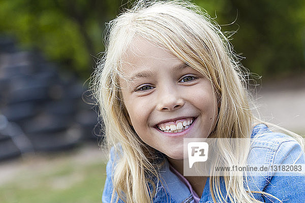Portrait of smiling blond girl outdoors