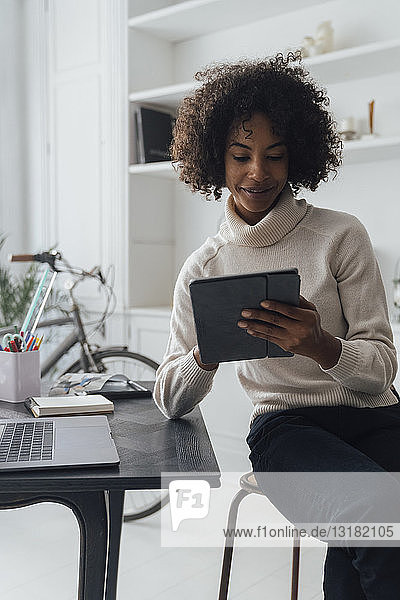 Mid adult freelancer sitting at her desk  working with laptop and digital tablet