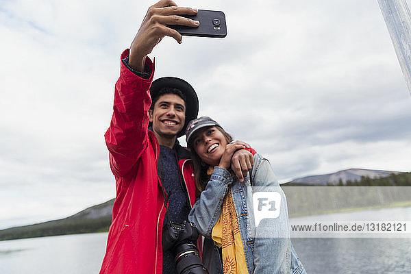 Finnland  Lappland  glückliches Paar beim Selbermachen an einem See