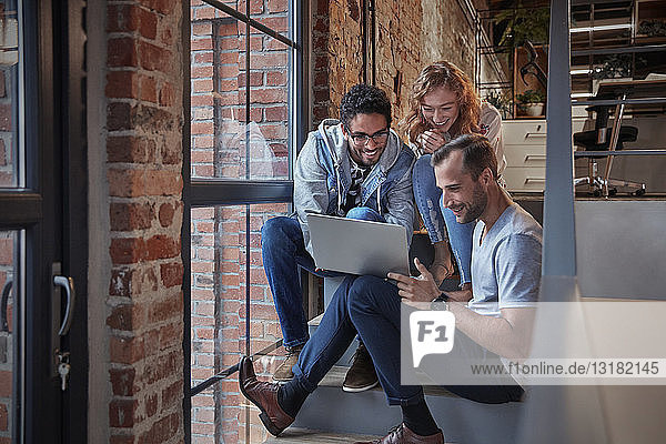Young business people sitting on stairs in loft office using laptop