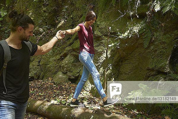 Spanien  Kanarische Inseln  La Palma  lächelnder Mann hält Hand der Freundin  die auf einem Baumstamm balanciert