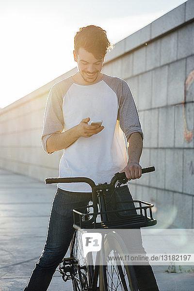 Lächelnder junger Mann mit Pendler-Fixie-Fahrrad schaut auf Handy