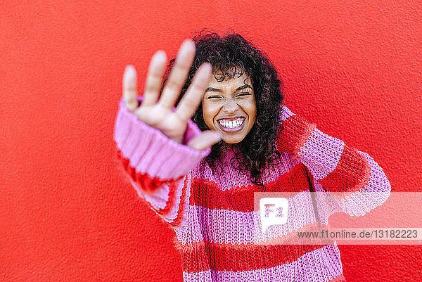 Porträt einer lachenden jungen Frau vor roter Wand