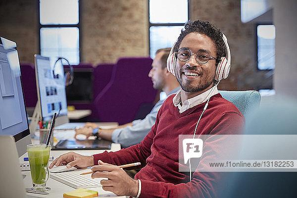 Junger Mann sitzt im Büro am Schreibtisch  trägt Kopfhörer und lächelt