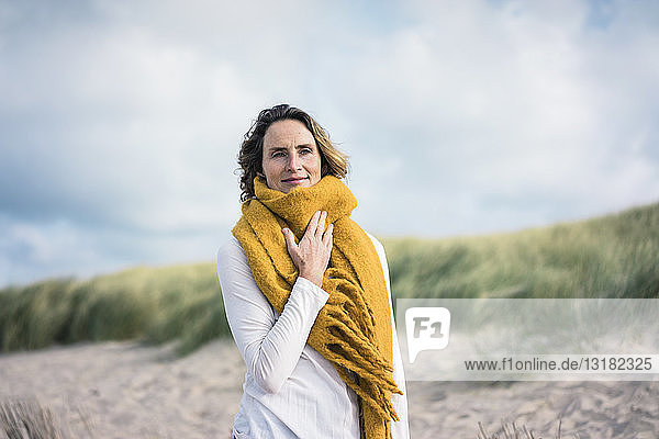 Mature woman relaxing in the dunes  enjoying the wind
