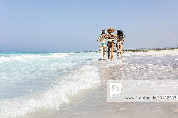 Glückliche Freundinnen  die mit umarmenden Armen am Strand spazieren