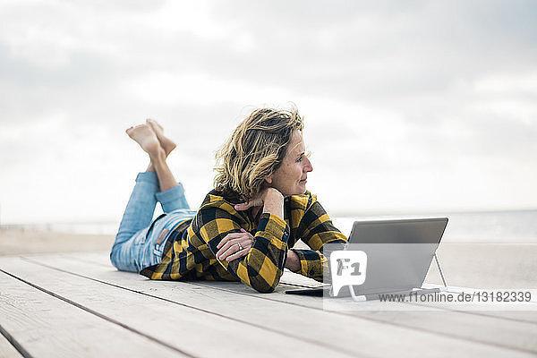 Reife Frau liegt am Strand auf der Strandpromenade und benutzt einen Laptop