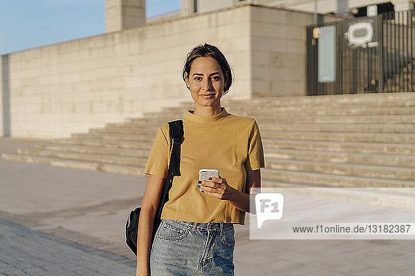Porträt einer lächelnden jungen Frau  die ihr Handy im Freien in der Hand hält