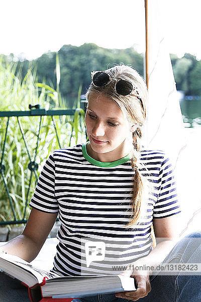 Young woman reading book at a lake next to sailing boat