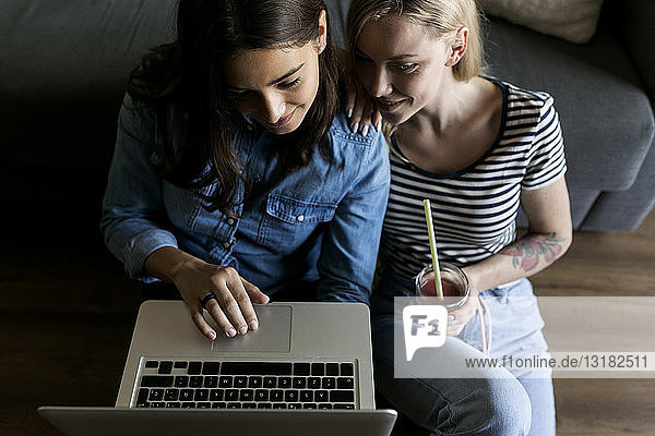 Two smiling young women sitting on floor with soft drink sharing laptop