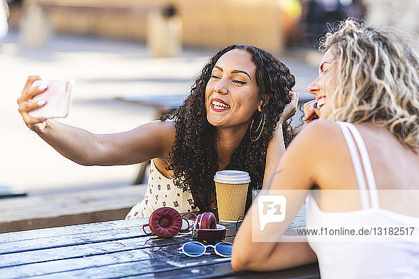 Two happy friends taking a selfie at table outdoors
