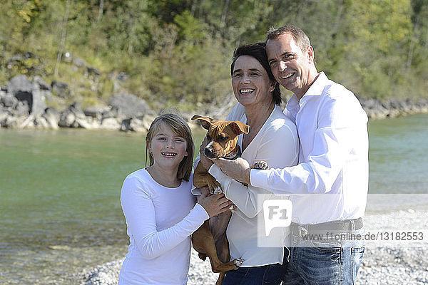 Glückliche Familie mit einem Hund an der Isar  Oberbayern  Deutschland