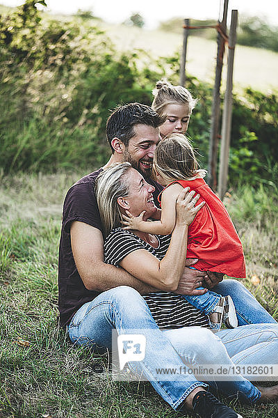 Happy family with two daughters sitting on a meadow