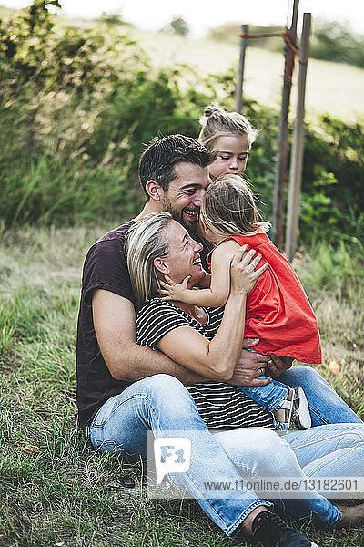 Glückliche Familie mit zwei Töchtern auf einer Wiese sitzend