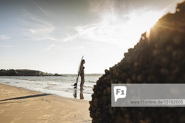 Frankreich,  Bretagne,  junge Frau mit Surfbrett am Meer stehend